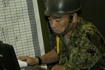 Japan Ground Self-Defense Force Maj. Nishikawa Hajime analyses data transmissions on a computer at the Camp Naha gymnasium, Okinawa, 23 July 2014. (Photo: US Marin Corps/ Lance Cpl. Pete Sanders).